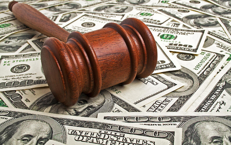 Wooden gavel laying on American dollars
