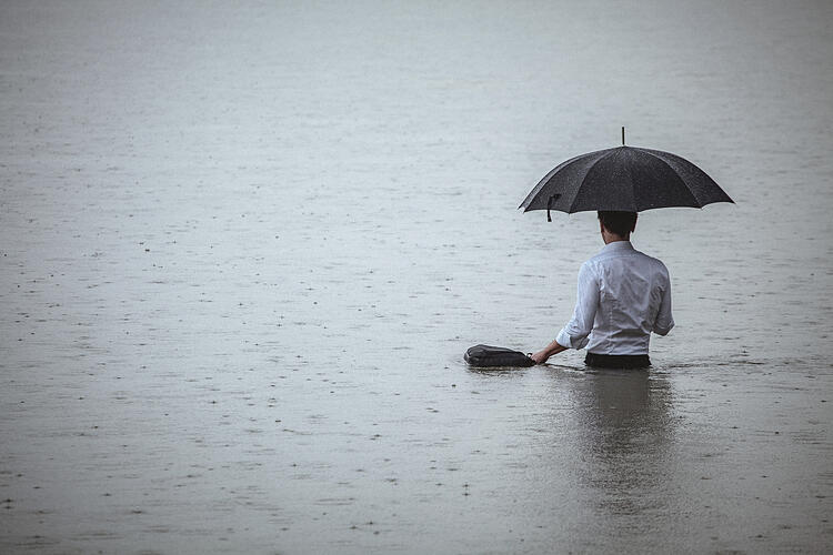 man standing in water and holding umbrella during rain