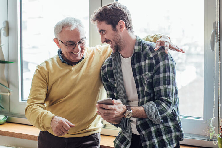 Father and son laughing and using phone