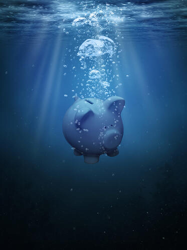 Piggy bank drowning in the ocean