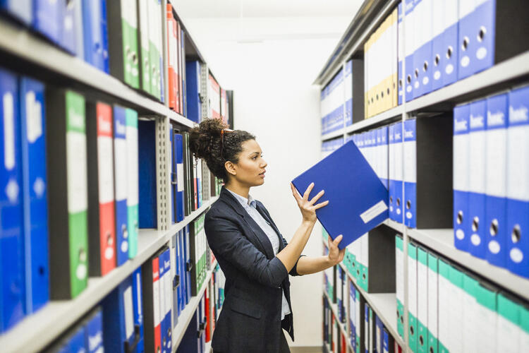 Woman searching for retirement plan files in paper archive