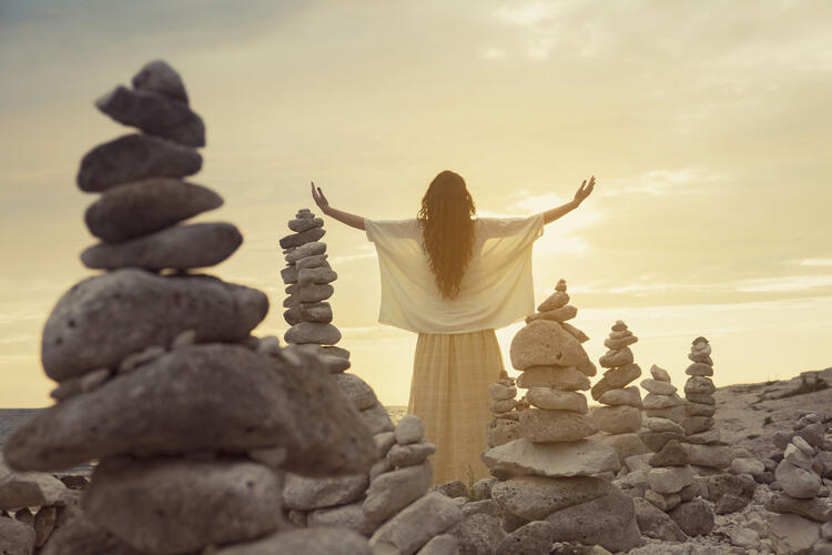 Woman with arms outstretched at sea in the middle of stacked rocks.