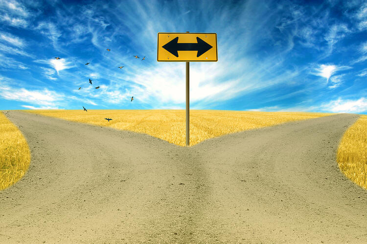 two roads, road sign ahead with arrows blue sky background.