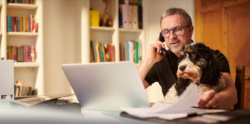 Man on the phone at desk with laptop and dog budgeting for retirement