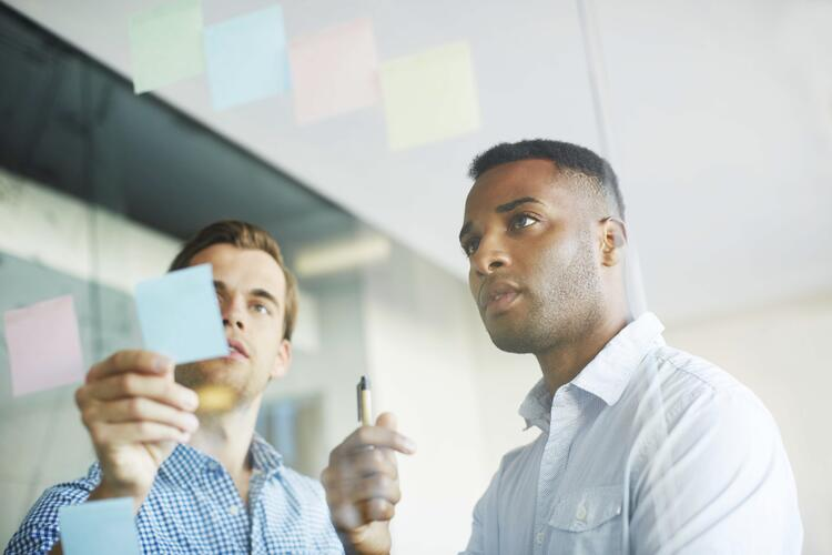 Two business colleagues discussing pass and fail notes on a transparent wall